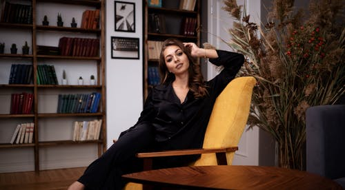 Stylish woman in black clothes sitting gracefully on armchair