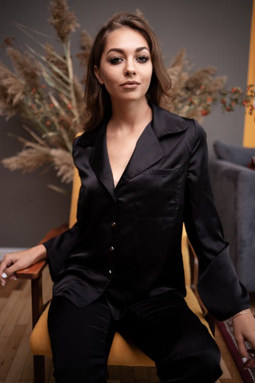 Young attractive female in black silk suit sitting on soft chair in stylish interior and looking at camera contentedly