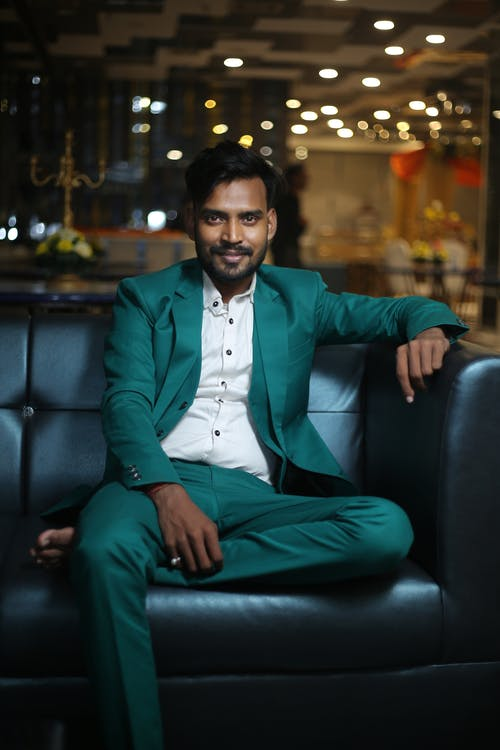 Stylish Indian man sitting on couch