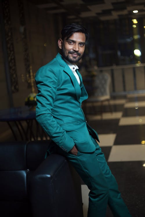 Side view of Indian male in trendy outfit standing in restaurant with hand in pockets and looking at camera