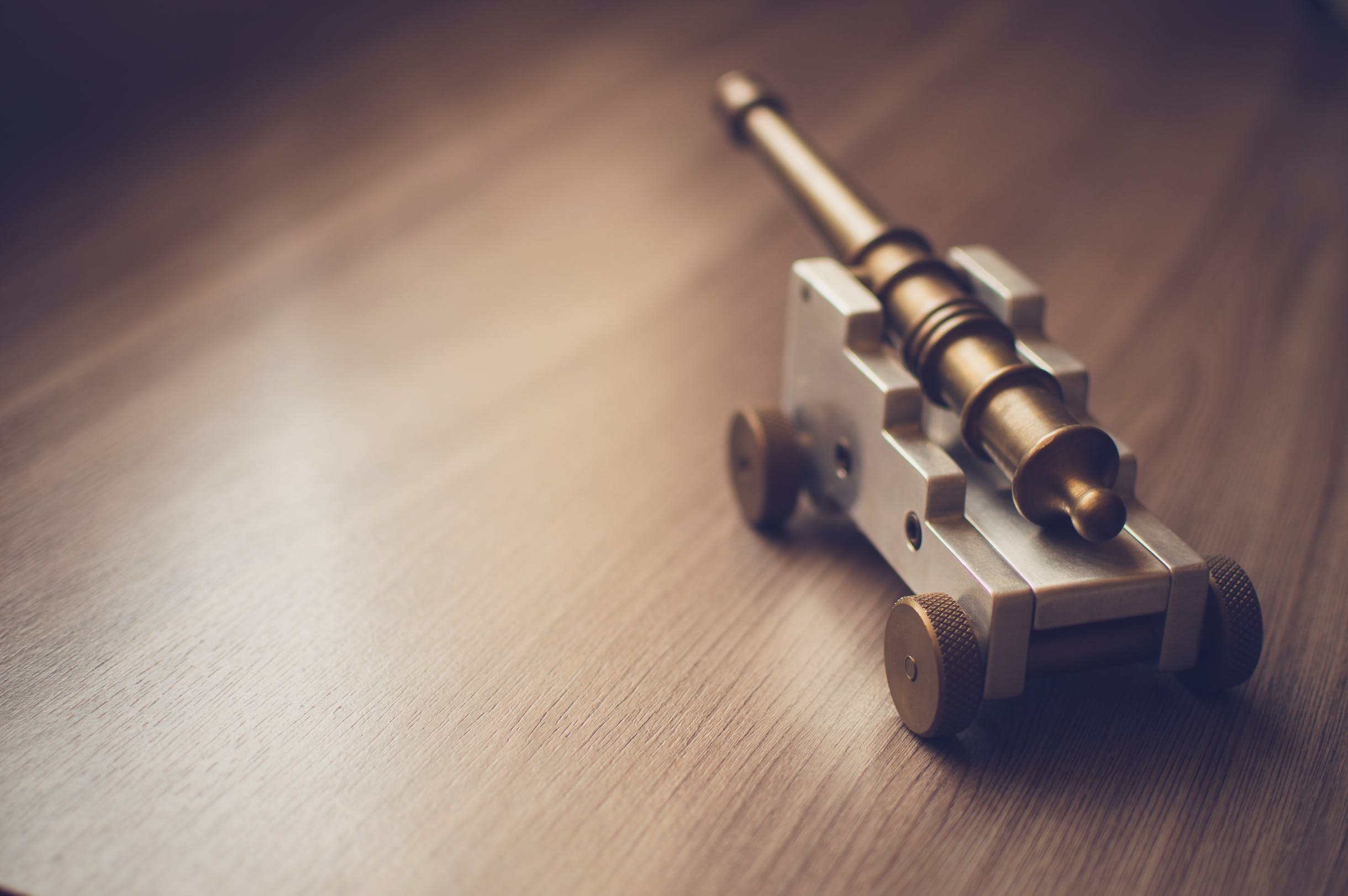 Grey Toy Cannon on a Beige Wooden Surface