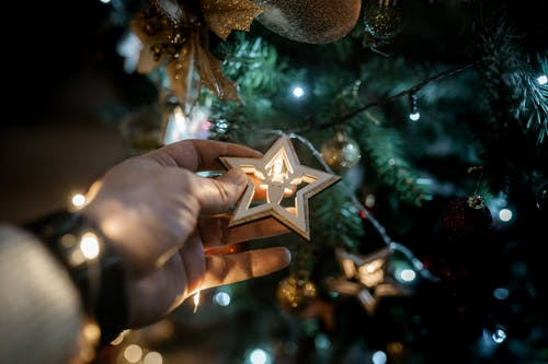 Crop man showing star decor on Christmas tree