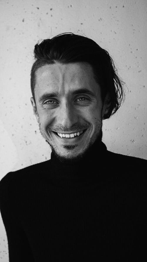 Grayscale Photo of a Man in Turtleneck Sleeves Smiling