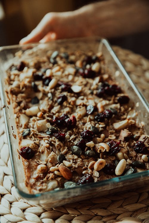 Crop person with granola in baking dish at home