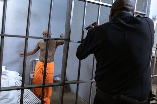 Uomo In Giacca Nera E Pantaloni Arancioni In Piedi Accanto Al Recinto Di Metallo Grigio