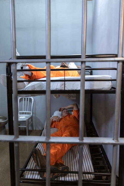 Man in Orange Jacket Lying on Bed