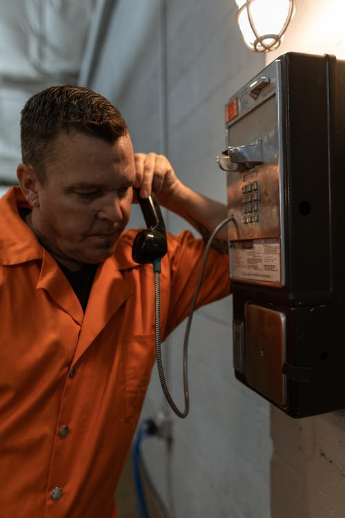 Uomo In Orange Button Up Shirt Holding Telephone