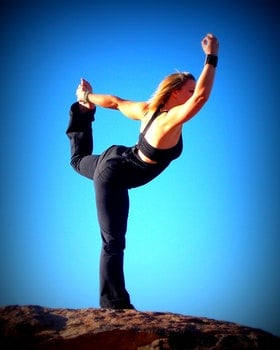 Woman in Black Sports Bra and Black Pants Exercise over the Brown Stone during Daytime