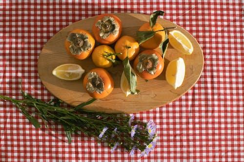 柿子與洋甘菊花附近的木板上的橘子