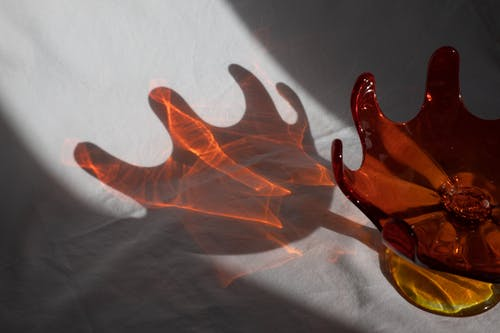 Shadow of unusual red transparent vase