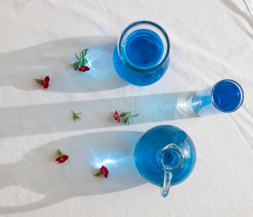 Top view of composed blossoms and various vases and glass with blue aqua on white fabric in sunlight