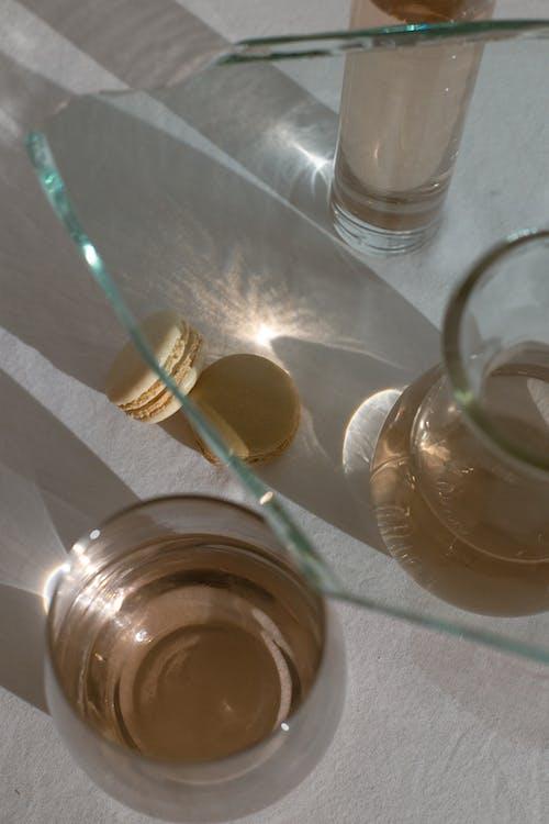 Macarons among glassware in sunlight