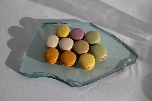 From above of broken piece of glass on white fabric with arrangement of delicious macaroons on top
