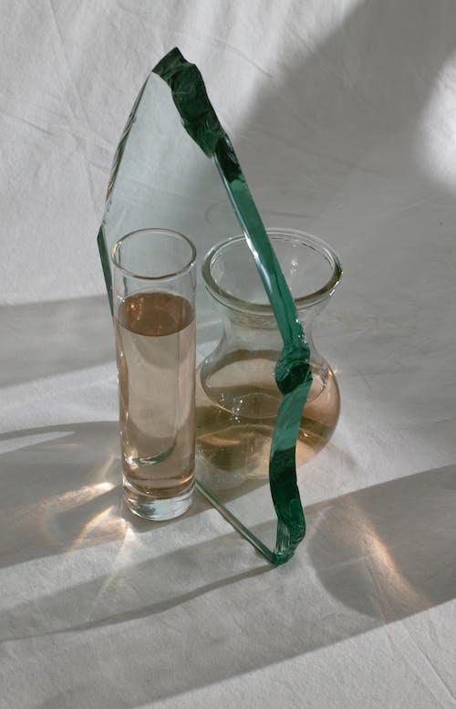 Glass chunk among vases on white fabric