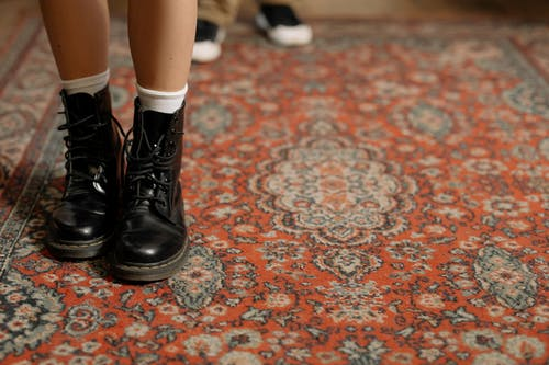 Woman in Black Leather Boots Standing on Red and White Floral Area Rug