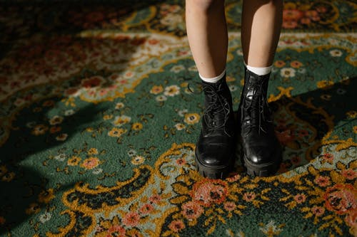 Woman in Black Leather Boots Standing on Green and Brown Area Rug