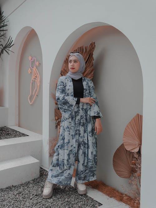 Stylish Muslim woman in hijab standing near arched wall