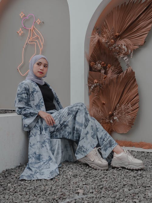 Full length positive young Islamic female in traditional headdress and trendy modest wear sitting gracefully in backyard and looking away dreamily