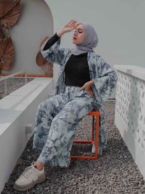 Fashionable Muslim woman sitting gracefully on chair
