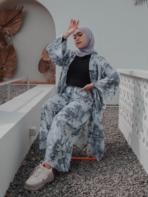 Full body fashionable young Muslim female in headscarf and stylish modest clothes sitting with arm raised and hand on waist on contemporary cottage backyard