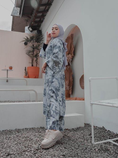Stylish Muslim woman standing graciously on backyard