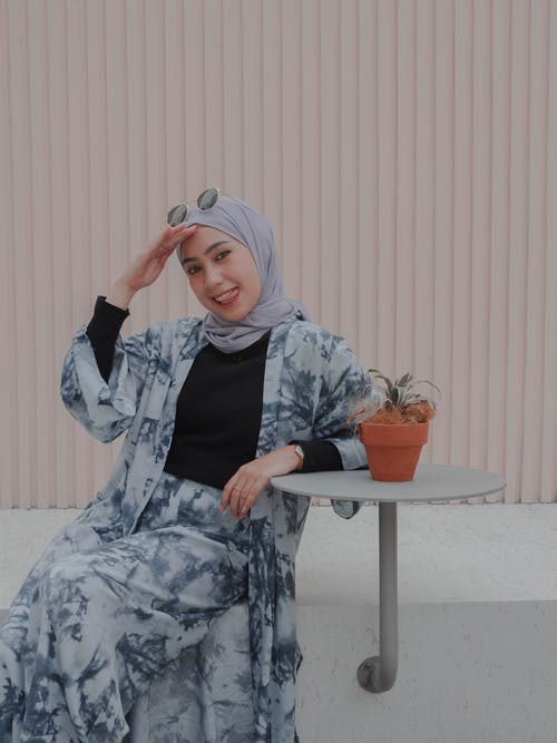 Cheerful young Muslim female in hijab and trendy clothes touching face and looking at camera with smile while sitting at table on backyard