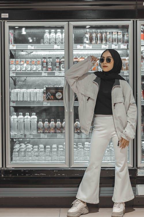 Trendy ethnic lady adjusting sunglasses in supermarket