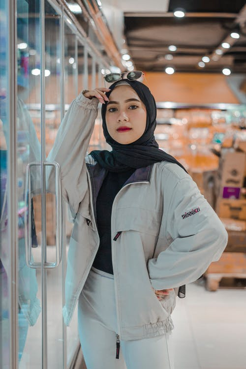 Confident young ethnic lady in stylish outfit and traditional Muslim hijab leaning on fridge in modern supermarket and looking at camera
