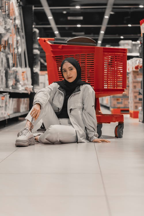 Full body of positive young Muslim lady in trendy outfit and hijab sitting on floor of modern hypermarket near shopping cart and looking at camera