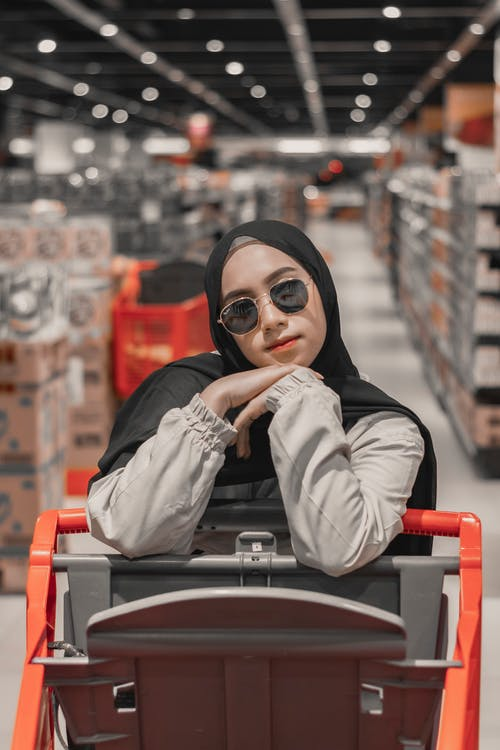 Pensive young Muslim female in stylish sunglasses and traditional hijab leaning on shopping trolley in contemporary supermarket