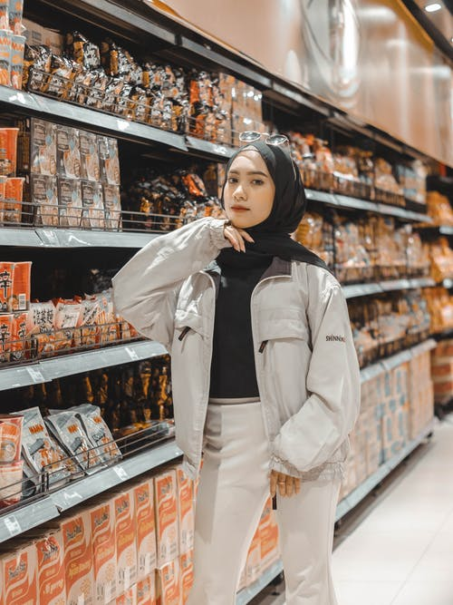 Confident young Muslim lady in stylish outfit and hijab standing near shelves in supermarket and choosing various products