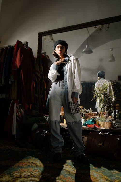 Hombre En Camisa De Manga Larga Con Botones Blancos Y Pantalones Negros De Pie Cerca De La Ropa