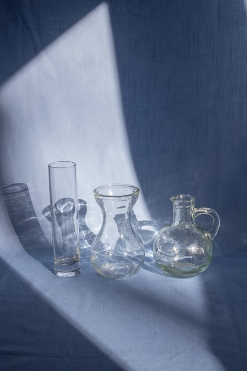 Collection of glass vases on fabric with shadows