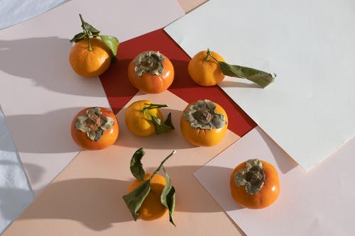 Persimmons and tangerines placed on sheets on table