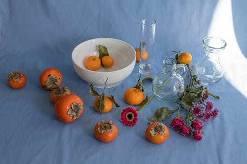 Arrangement of sweet ripe persimmons juicy mandarins and delicate pink flowers scattered on blue background near vases and white bowl