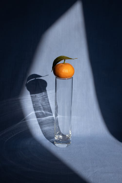 Mandarin placed on vase on blue surface