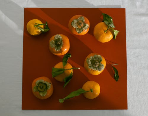 From above arrangement of ripe juicy persimmons and mandarins arranged on brown background on table in light studio
