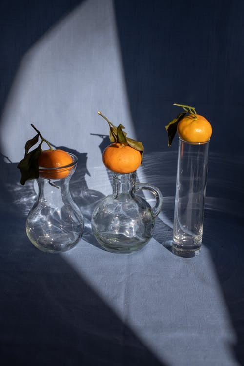 Creative composition of ripe organic mandarins placed on glass vases on blue surface in sunlight