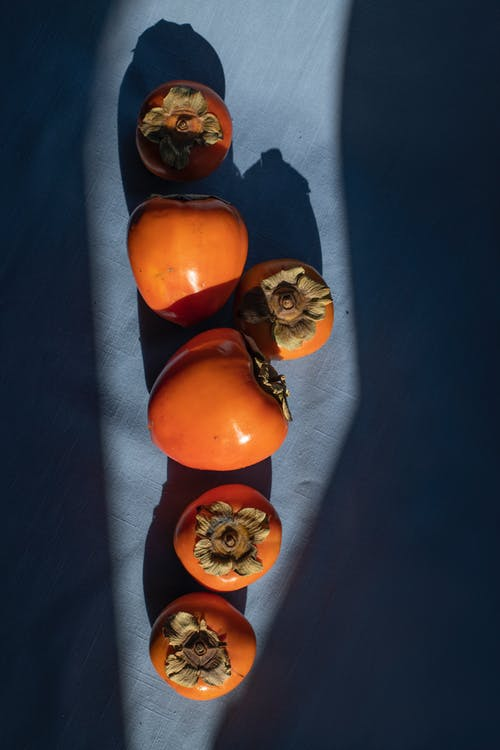 Delicious persimmons heaped on blue surface