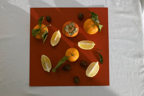 Composition of persimmons lemons and mandarins on table