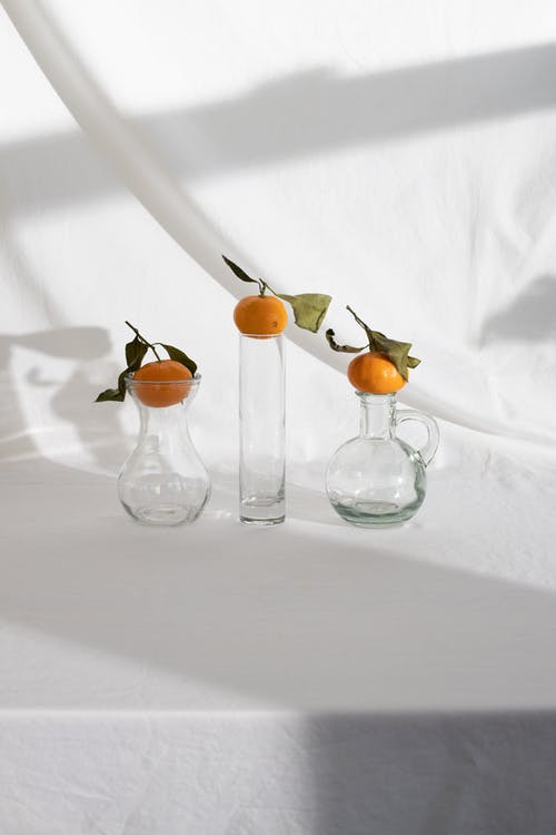 Creative arrangement of ripe juicy mandarins placed on glass vases on white fabric background in light studio