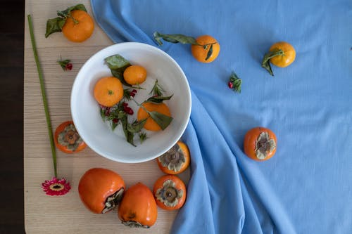 Composition of sweet persimmons and mandarins placed on table