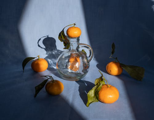 Fresh mandarins composition with glass decanter in kitchen