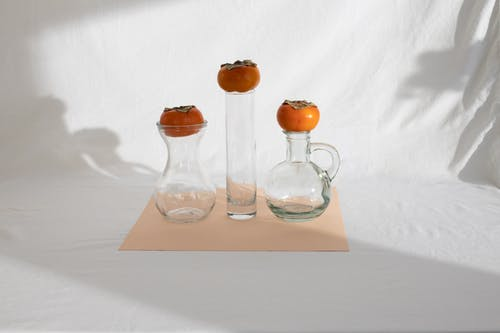 Composition of fresh ripe persimmons placed on glass vases of various shapes on white cloth in sunlight