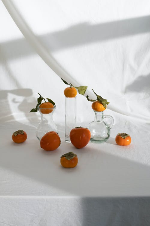 Composition of mandarins and persimmon placed on white table with glassware