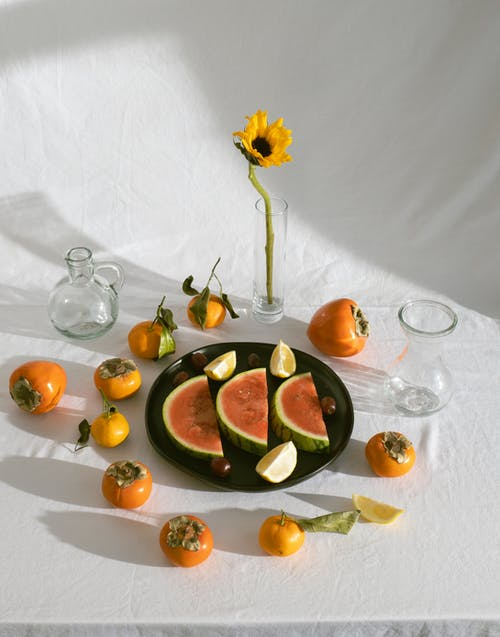 Composition of assorted exotic fruits and sunflower with glassware on white table
