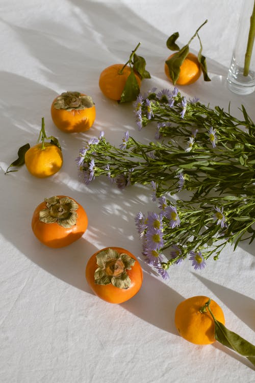 Aster amellus bouquet laced on table near assorted fresh fruits