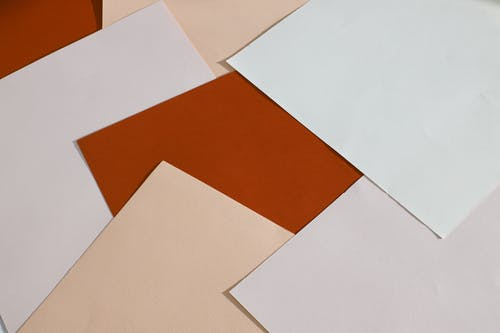 From above of blank paper sheets of different colors scattered on table as abstract background
