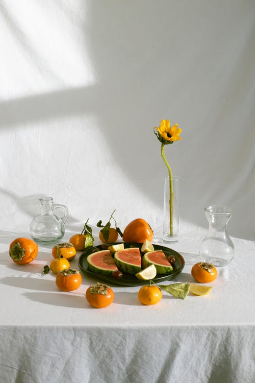 Assorted fruits scattered on table near watermelon plate and vases