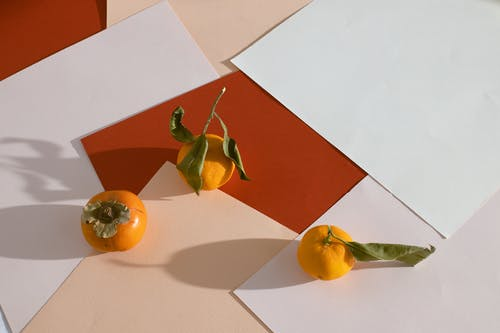Ripe persimmon with mandarins arranged on table with assorted scattered paper sheets